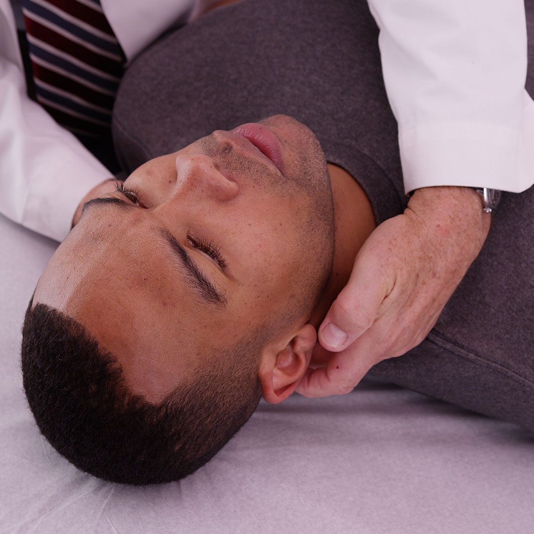 image of a man's head laying on a medical table with a doctor touching his neck