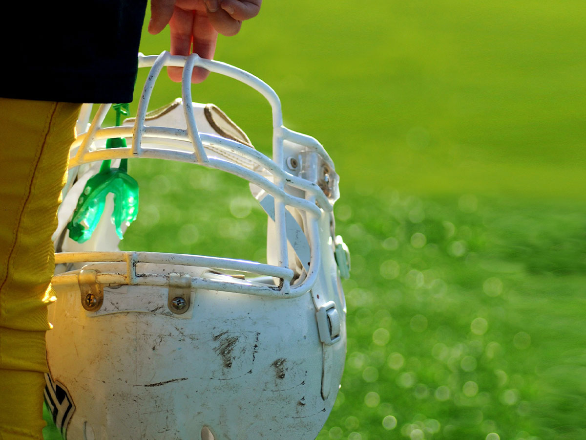 image of a person holding a football helmet