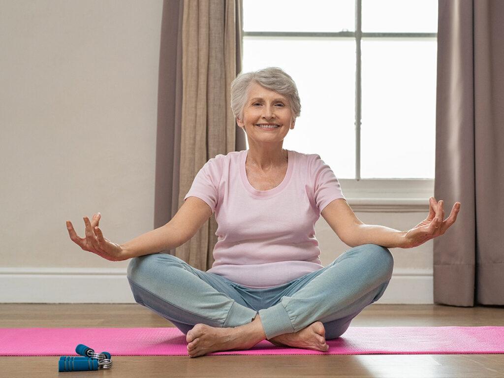 Senior smiling woman doing yoga in her living room.